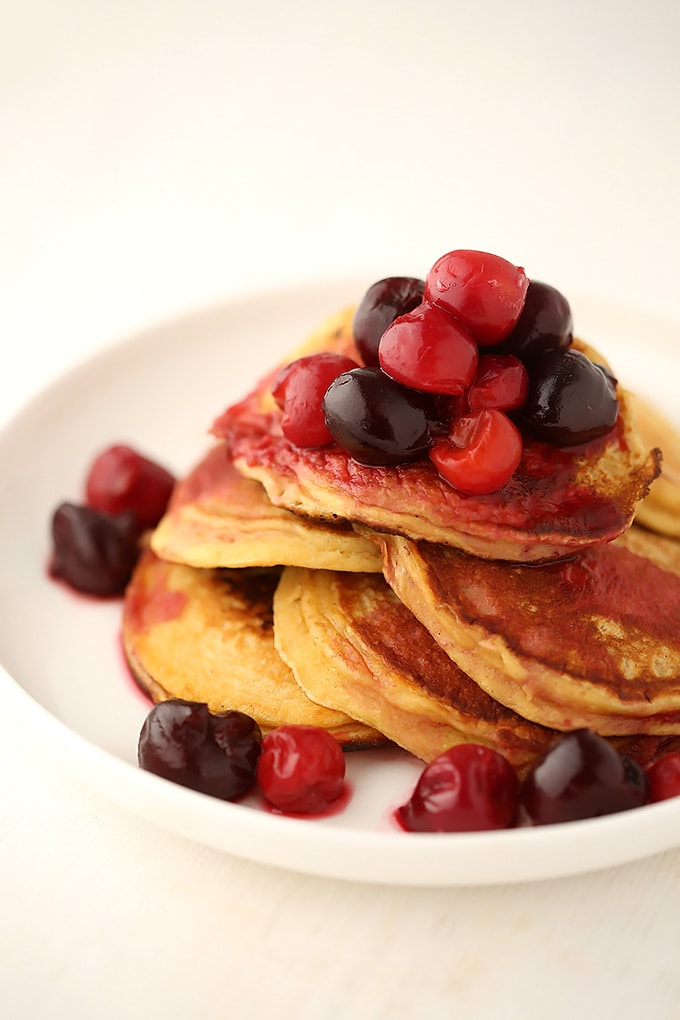 kefir pancakes topped with cherries stacked on a white plate