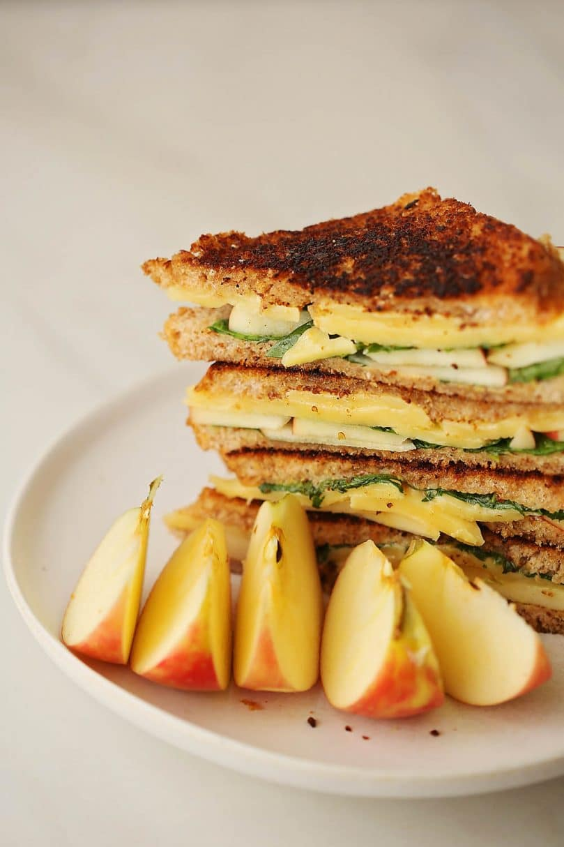 white plate served with sandwich and slices of apples