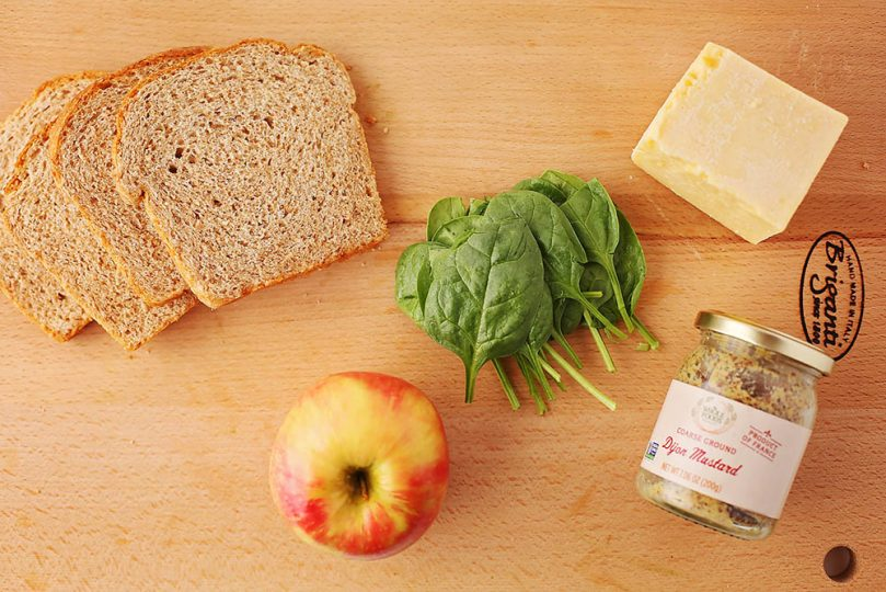 cutting board with ingredients to make cheddar apple panini