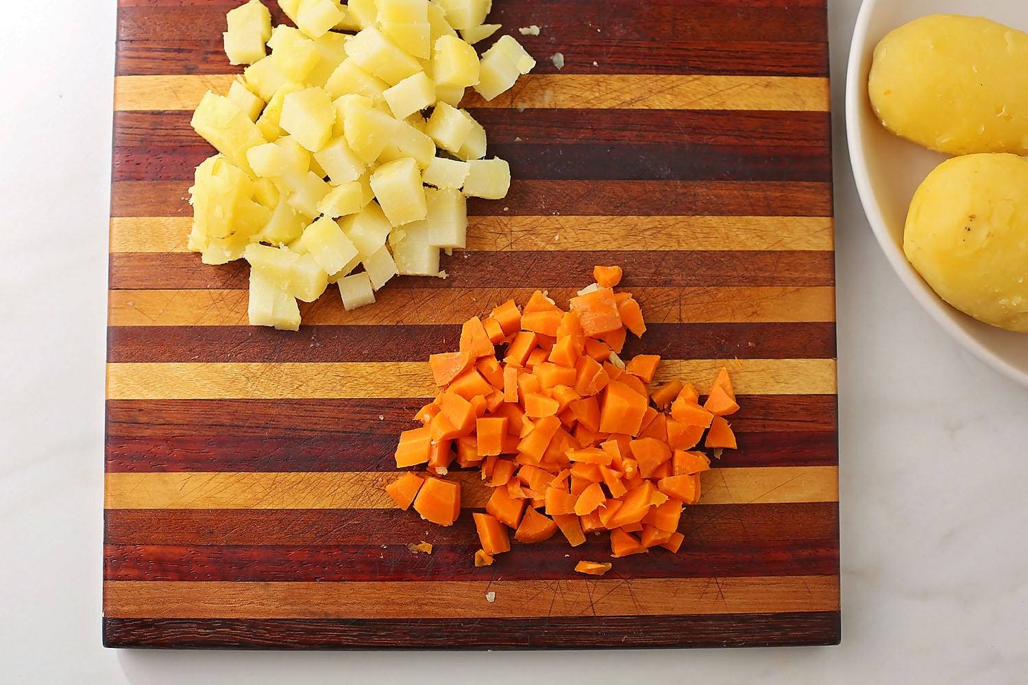 diced carrots and potato on the wooden cutting board