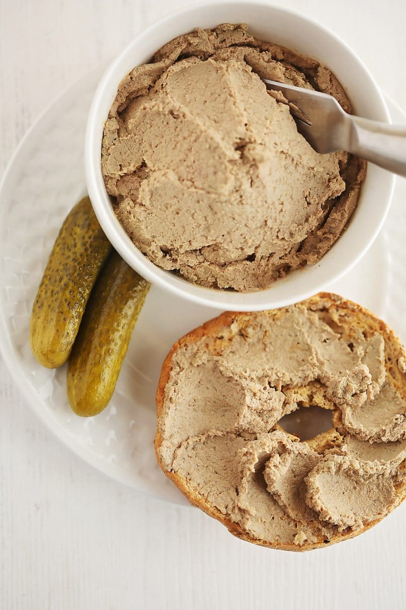 liver pate spread on top of the bagel with pickle next to it, and small white bowl filled with pate