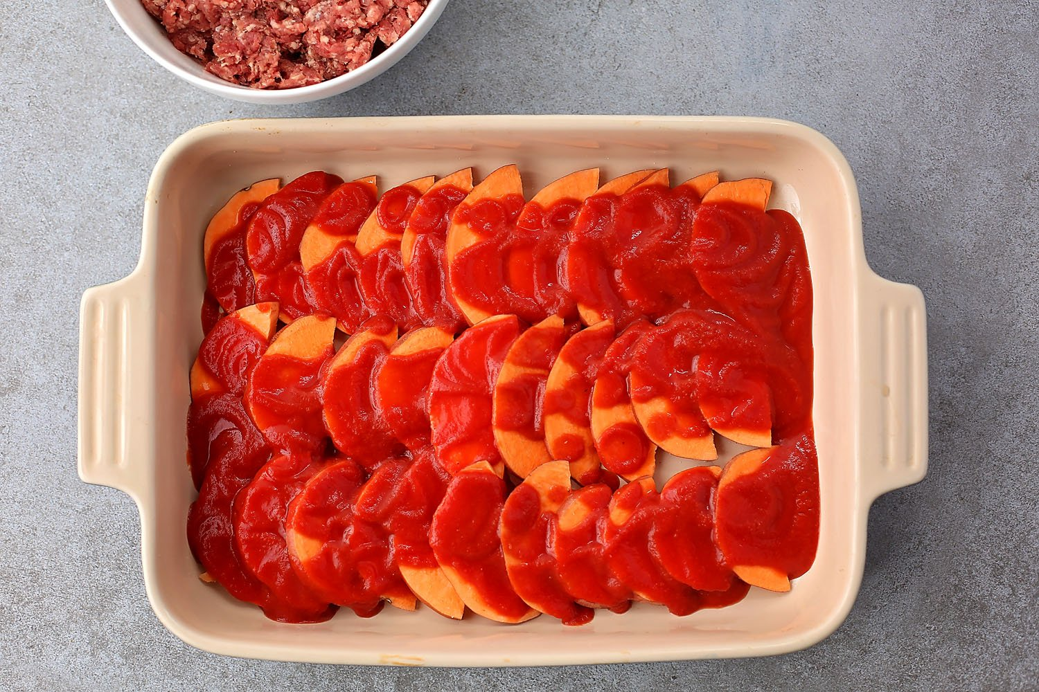 layered sweet potatoes in the casserole dish