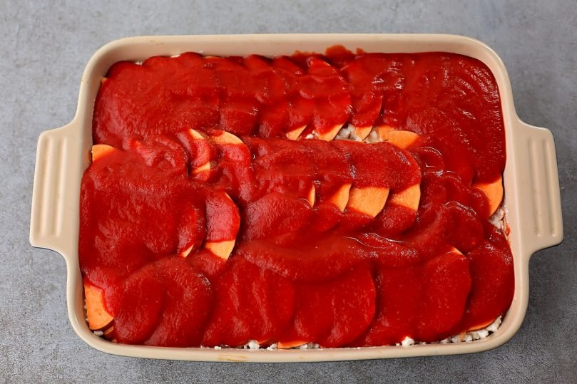 spreading tomato sauce over potatoes