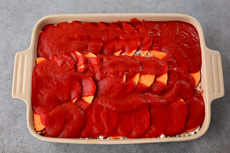 the making of Sweet potato lasagna, spreading tomato sauce over potatoes
