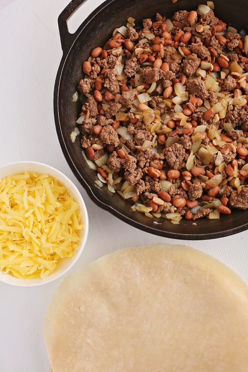 tabletop with skillet with browned meat and tortillas