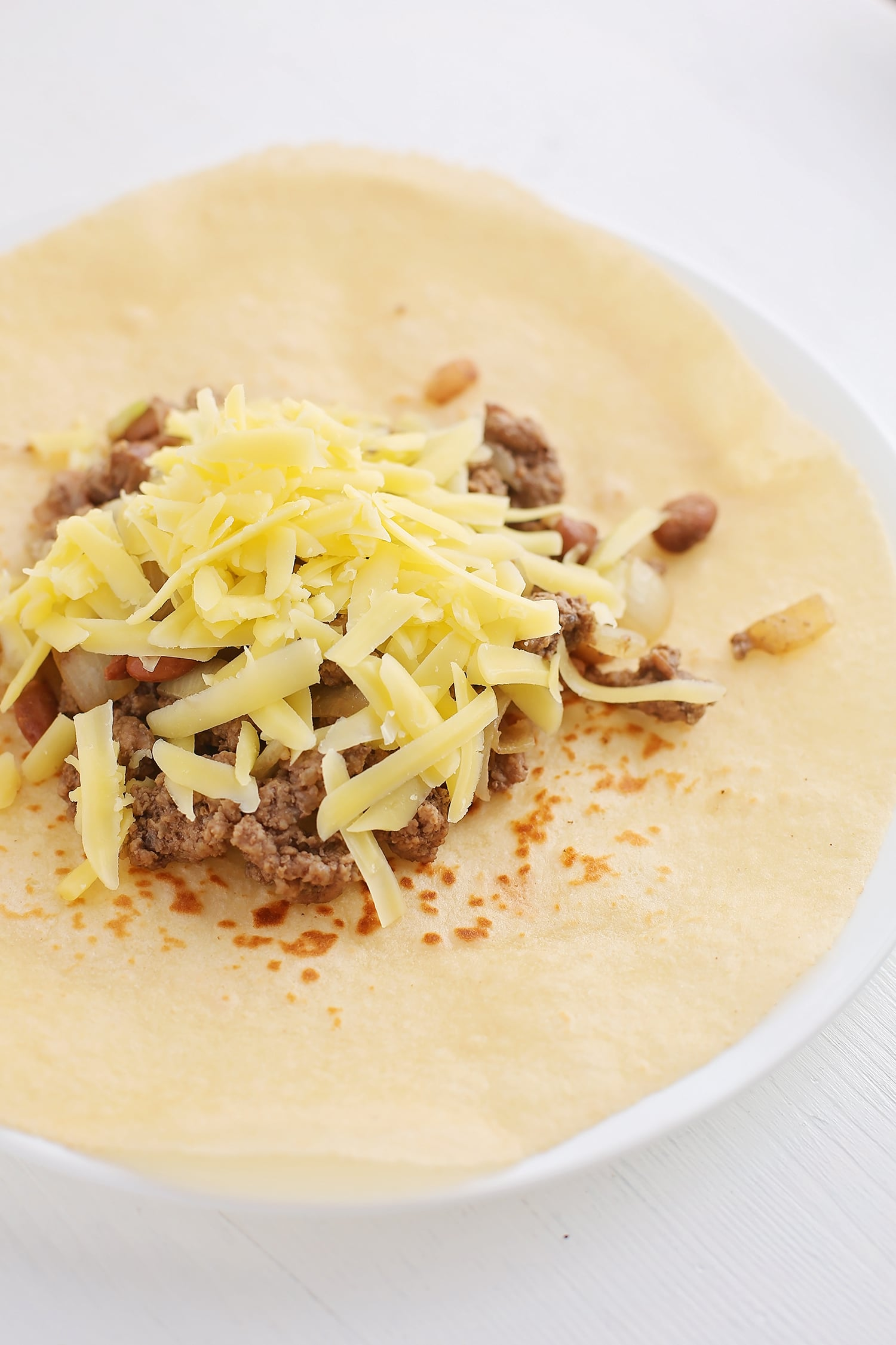 Tortilla with Beef and Sweet Onions, and shredded cheese on top, before wrapping