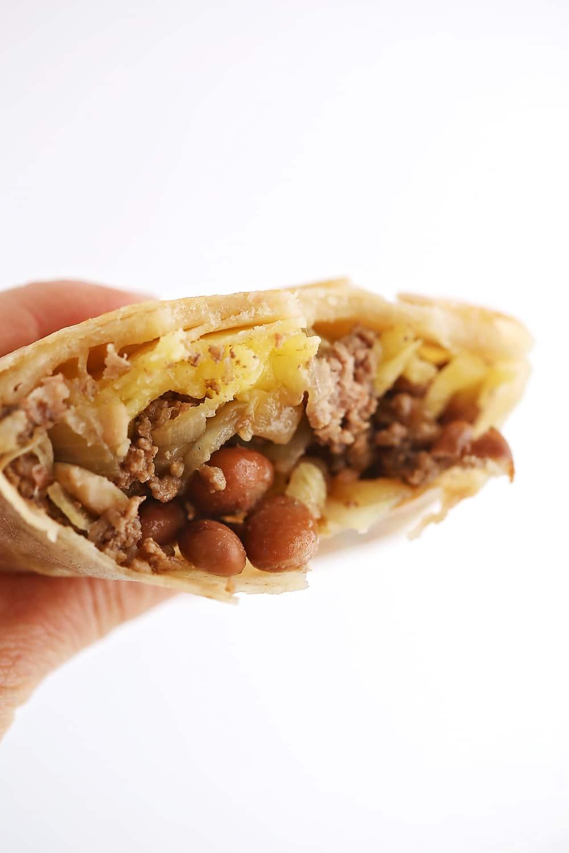 the hand holding the bitten stuffed tortilla