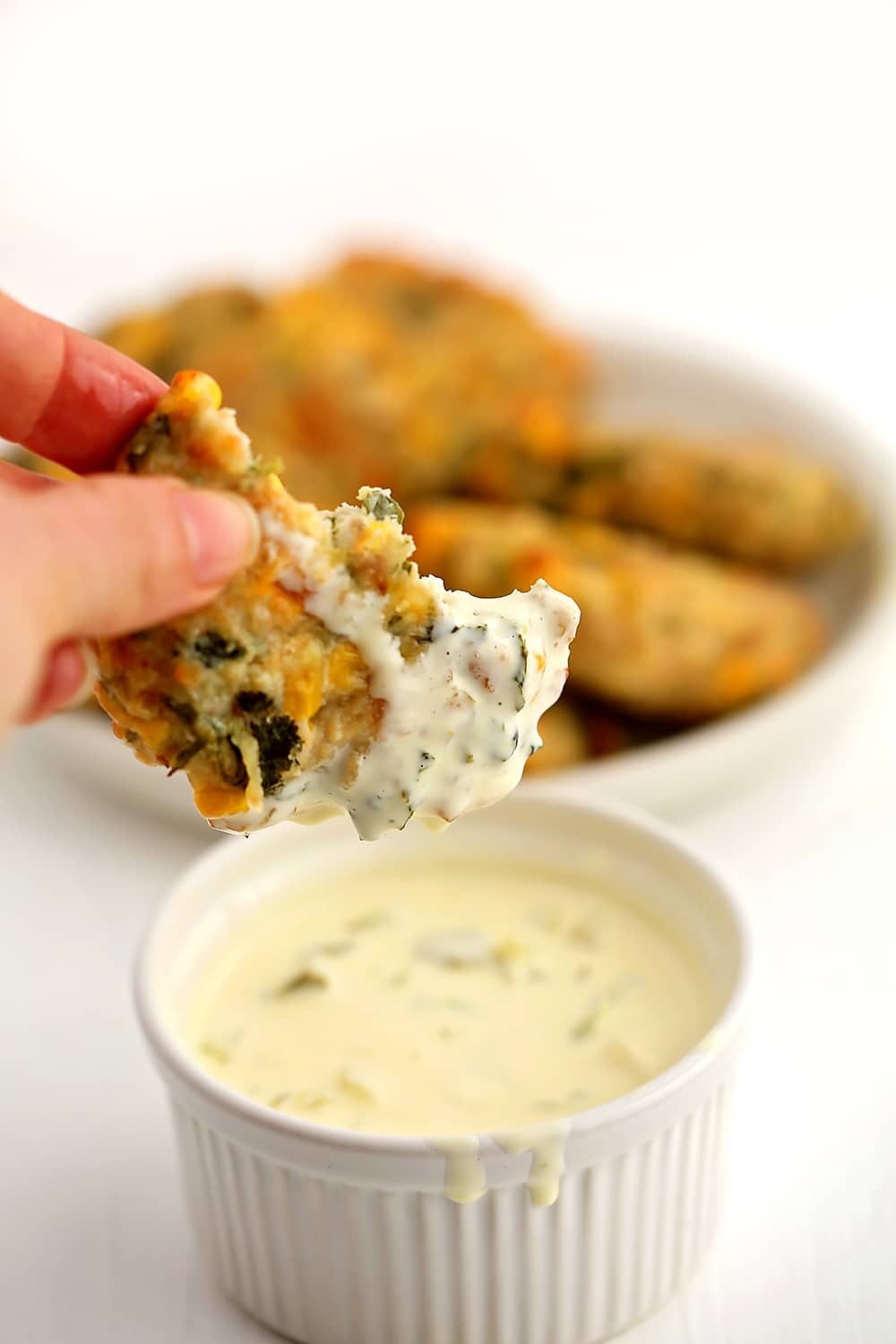 a hand holding a Chicken Fritter dipped in the tartar sauce