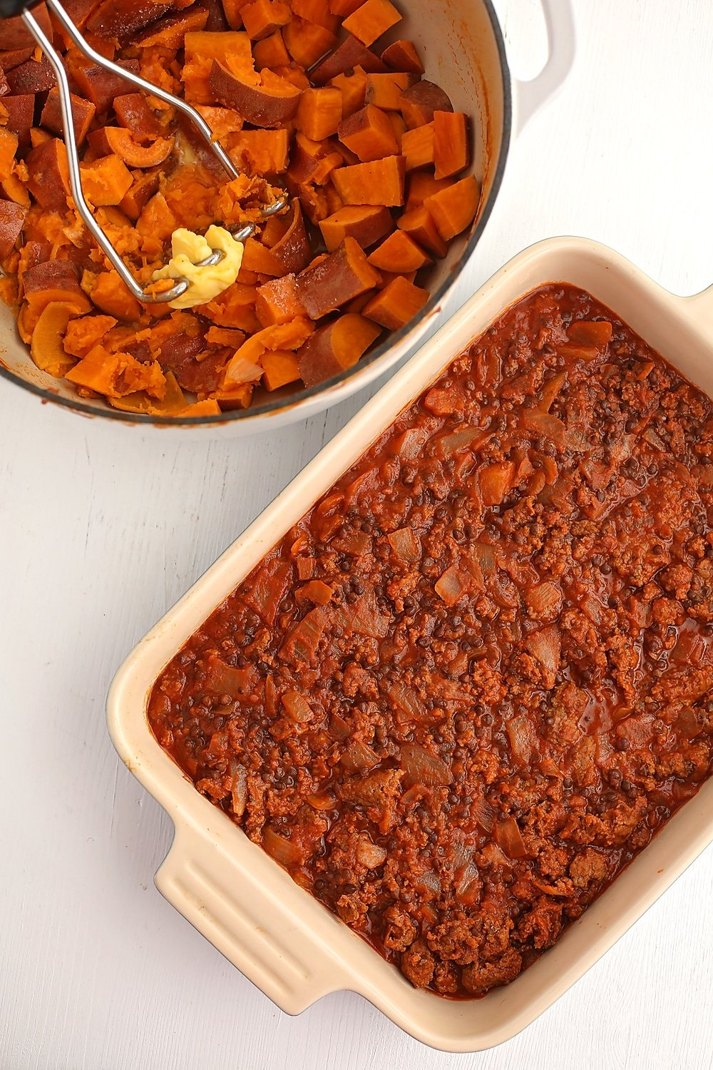 baking dish filled with cooked meat and pot filled with mashed sweet potato