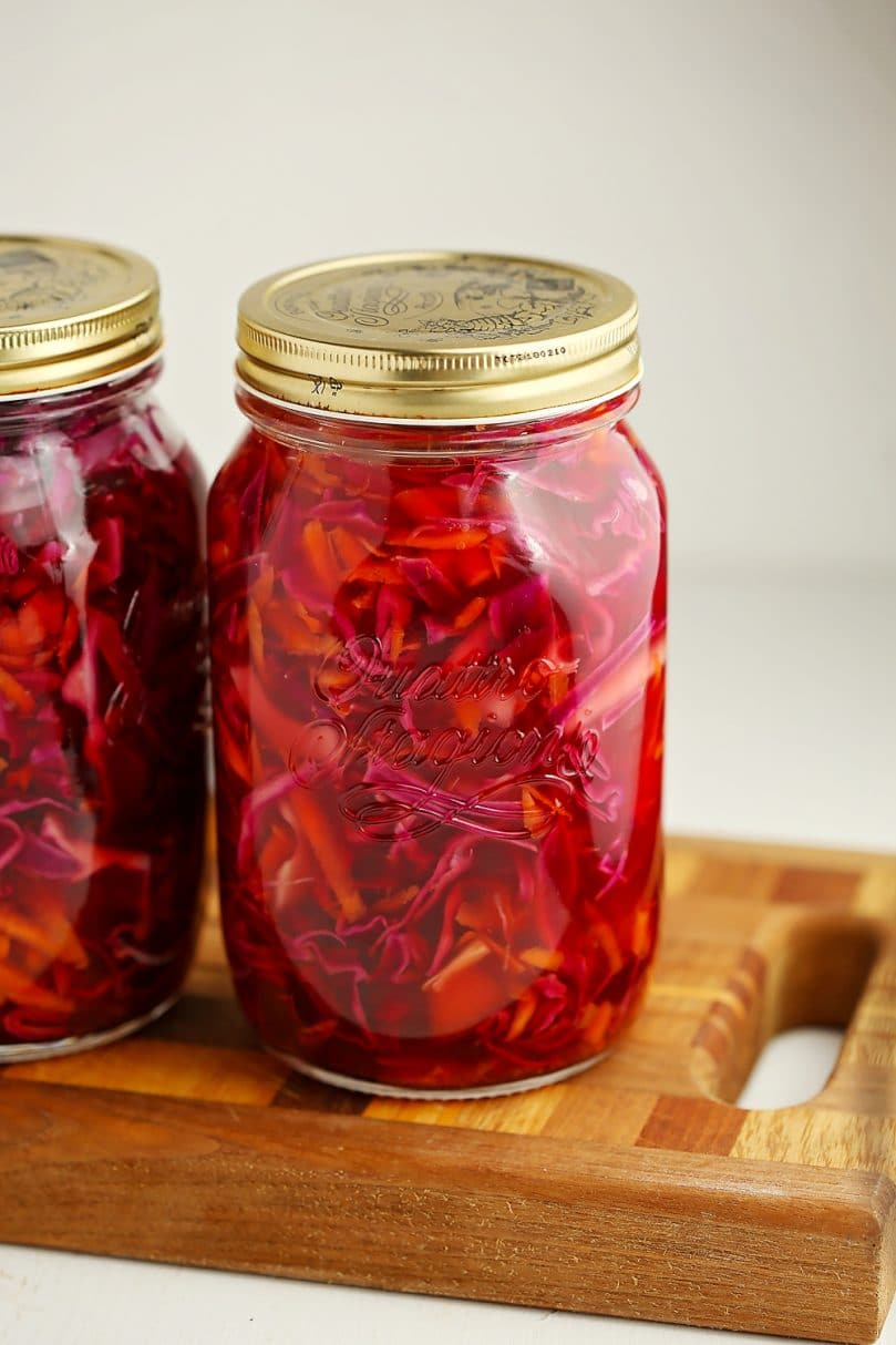two jars filled with pickled cabbage and carrots slaw