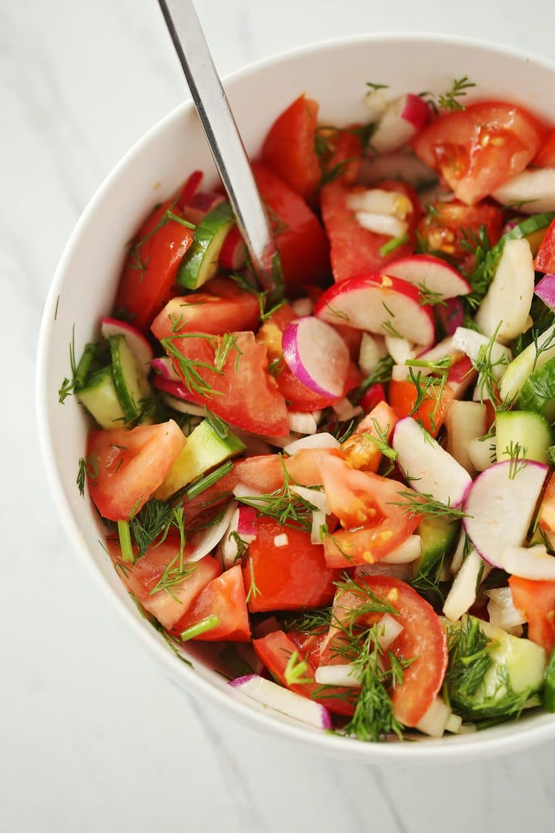 salad with dill served in a white bowl