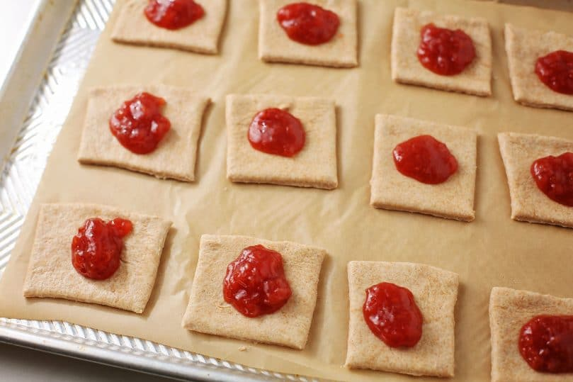 dough squares with a drop of jam laying on the baking sheet