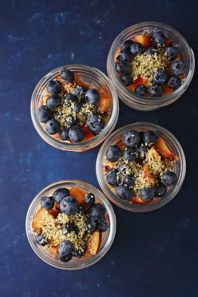 four mason jars filled with fruit and cottage cheese and sprinkled with hemp seeds