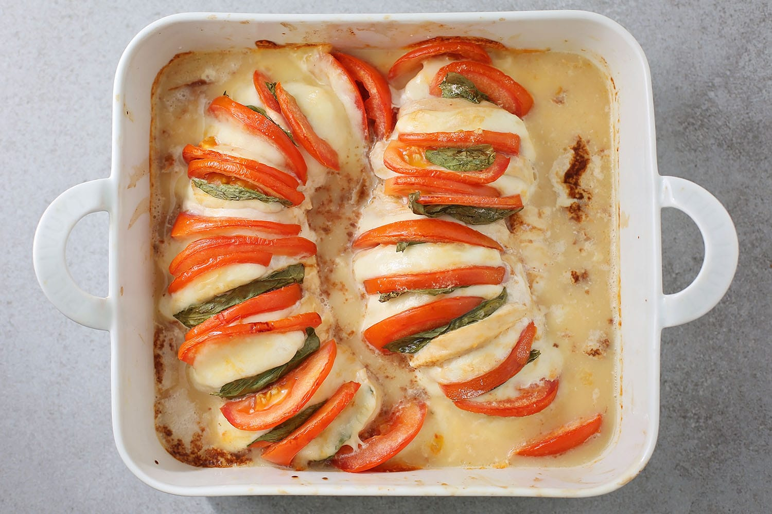 baked chicken with tomato slices and mozzarella
