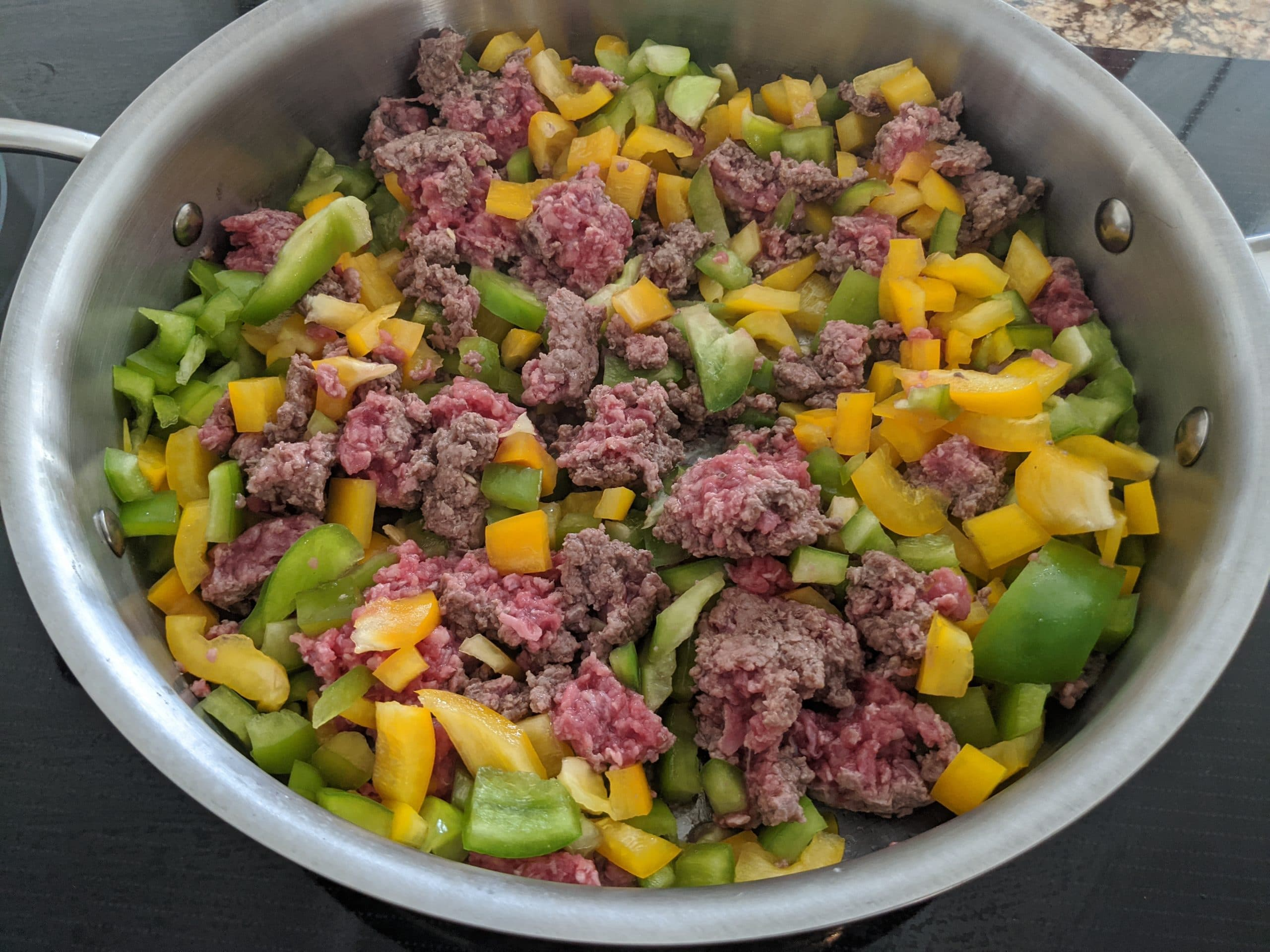 uncooked ground beef, peppers and rice cauliflower in the skillet