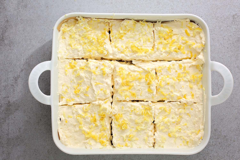 sliced lemon cream pie bars in a white dish