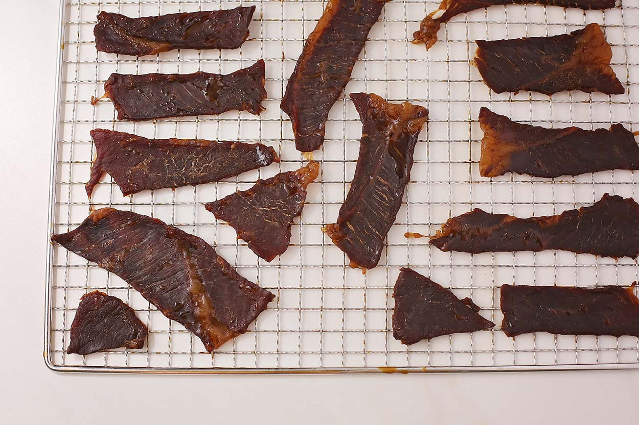 meat pieces arranged on oven-safe cooling wire racks
