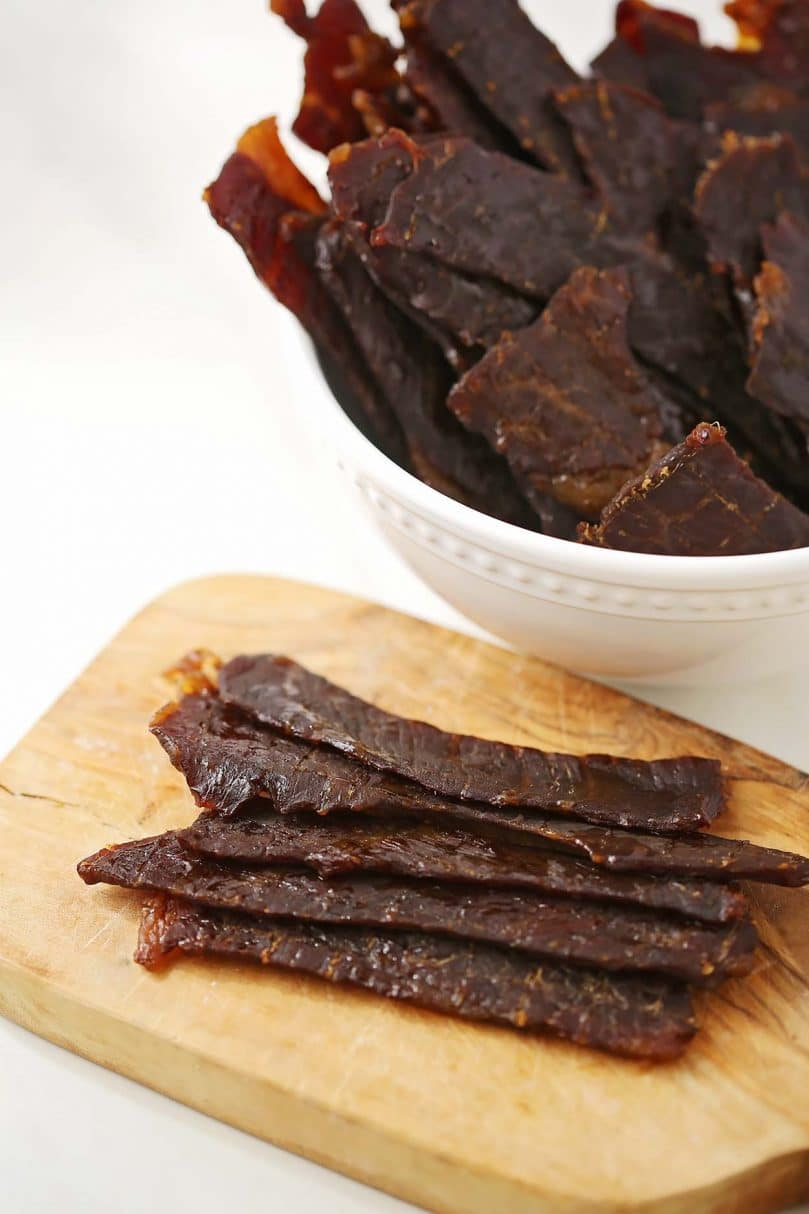 homemade beef jerky laying on wooden cutting board