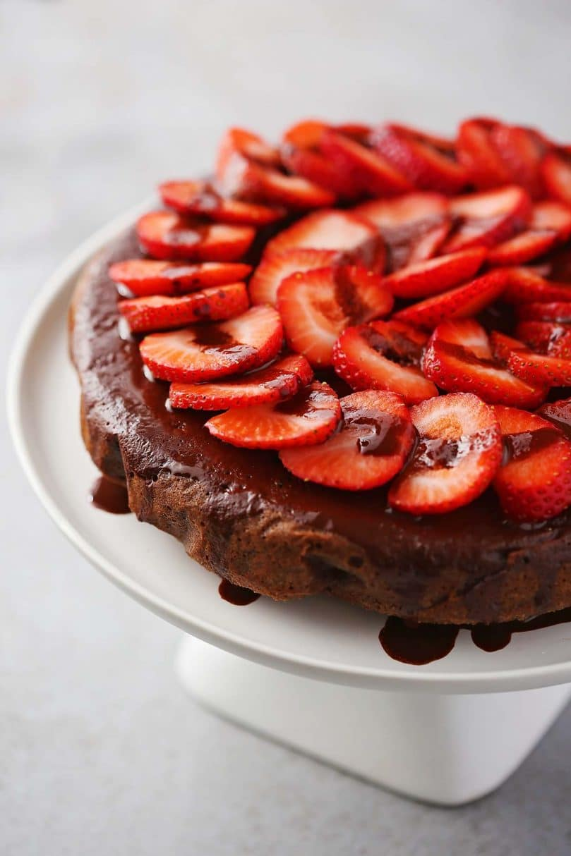 round chocolate cake with sliced strawberries on top served on a white cake stand