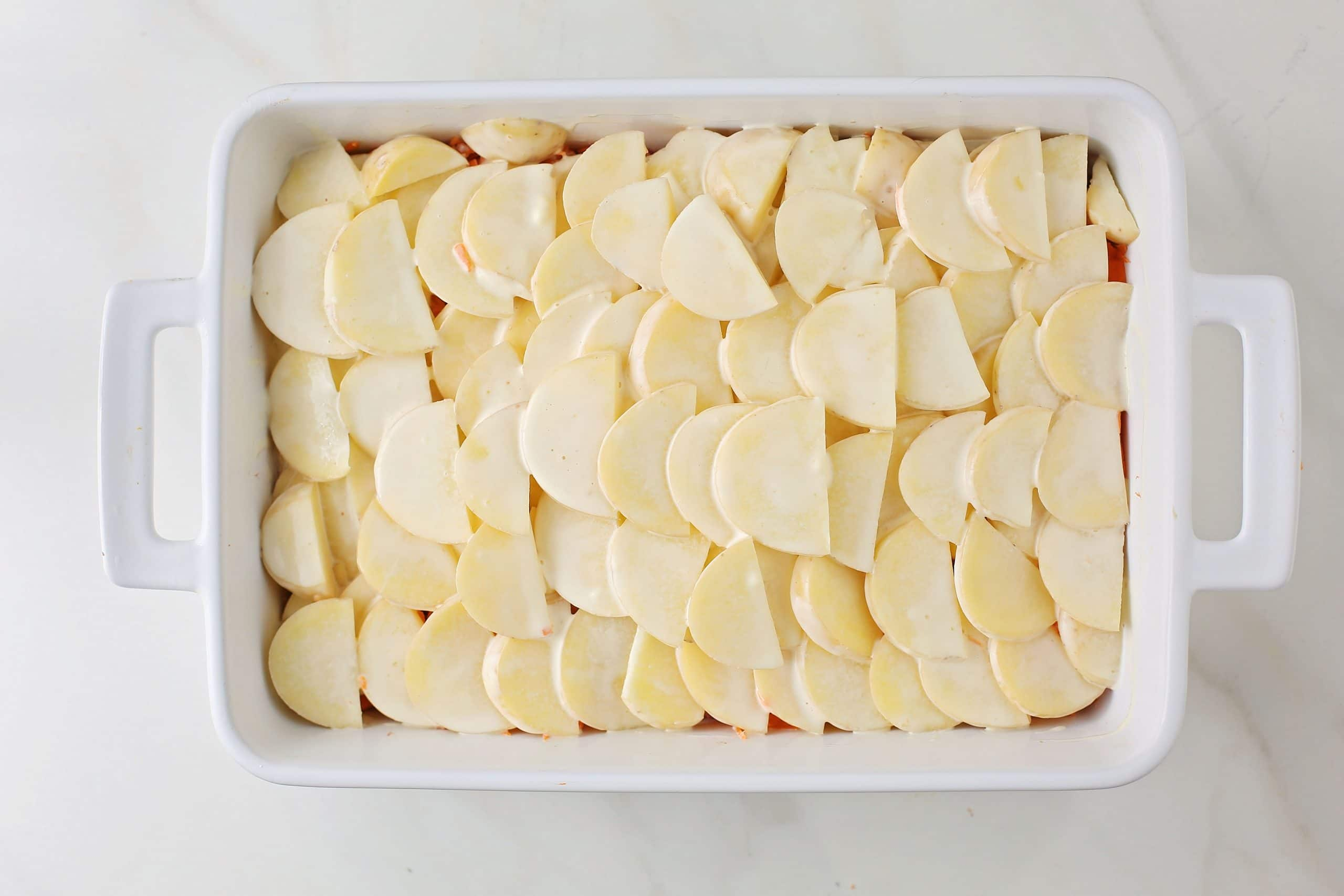 uncooked layer of potatoes in the making of casserole