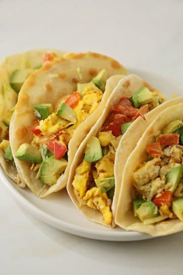 plate with tacos filled with scramble eggs and avocado