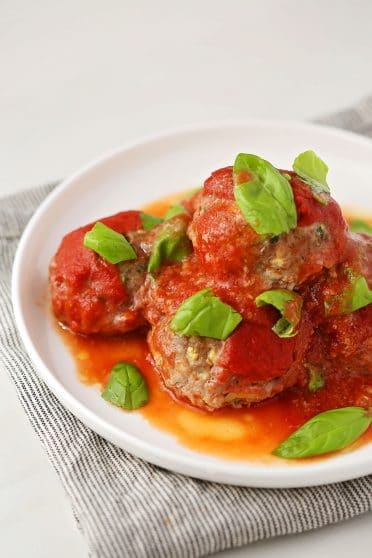 white plate with Zucchini Beef Meatballs topped with tomato sauce and fresh basil leaves