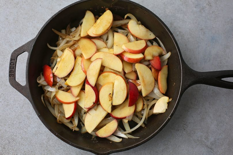 fried onions and apples in the skillet