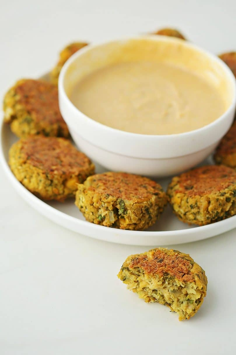 Oven-Baked Easy Falafel on a white plate with tahini dip in the bowl