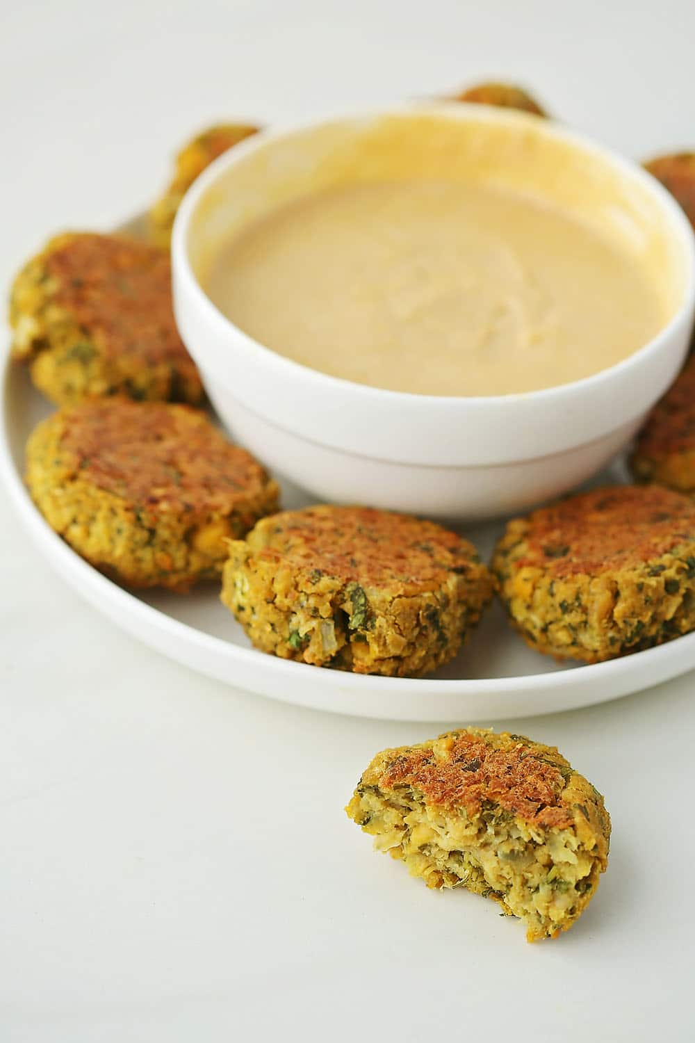 white plate with falafels and bowl with dipping sauce