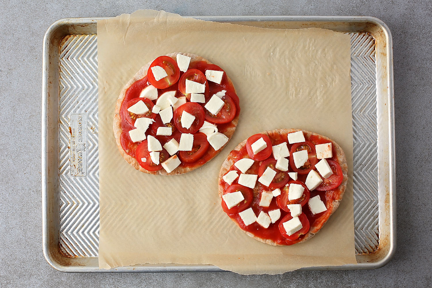 sheet pan with two pita pizzas with mozzarella before going in the oven