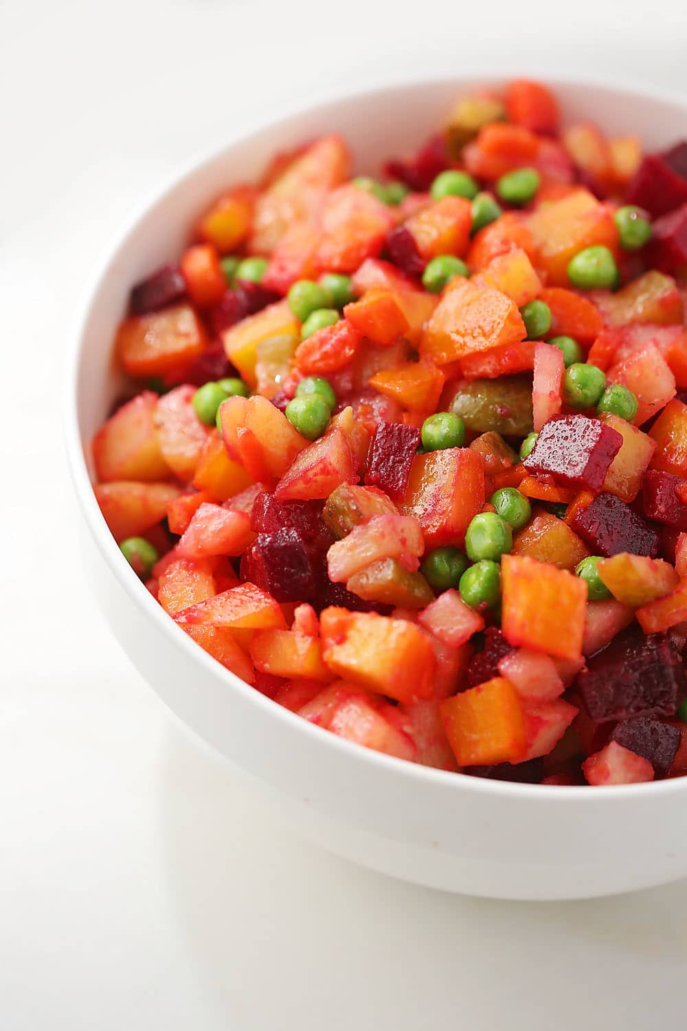 a white bowl filled with the salad with beets and pickles