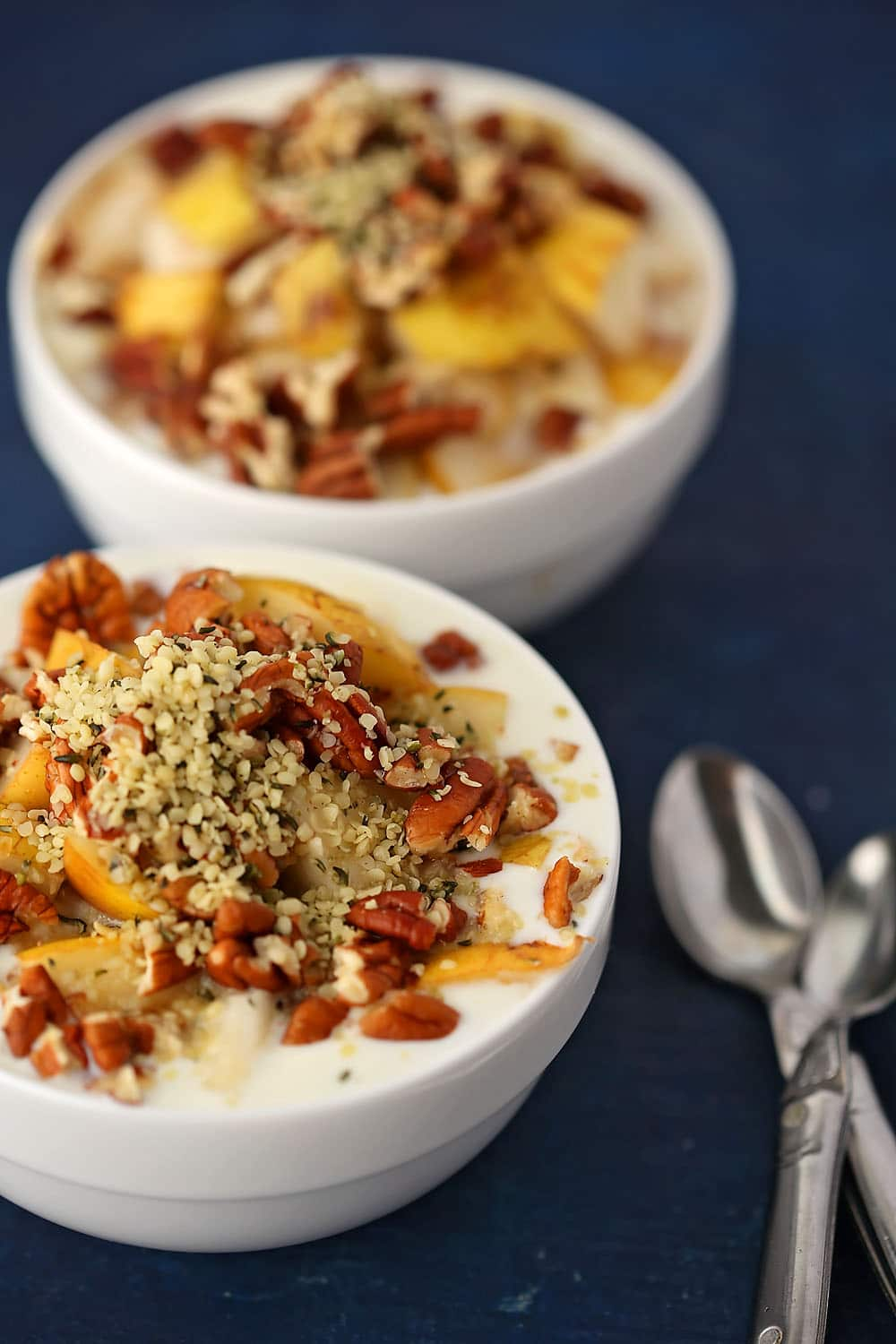 two small white bowls filled with Yogurt Parfait with Pear and Pecans