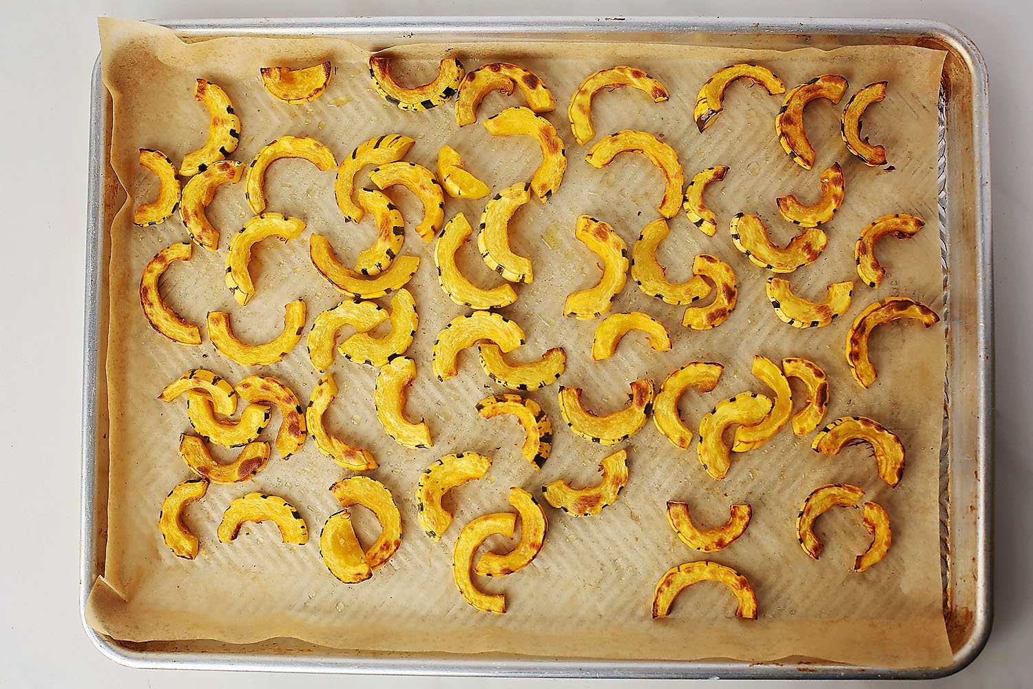 Baked delicata squash slices on the sheet pan