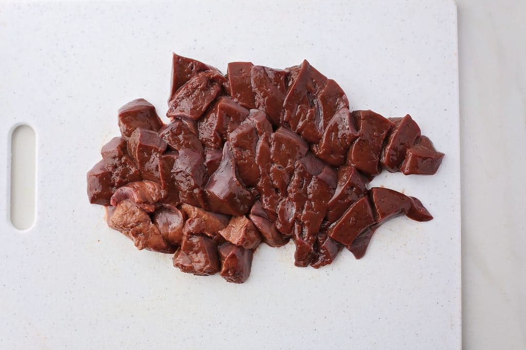 sliced raw liver on white cutting board