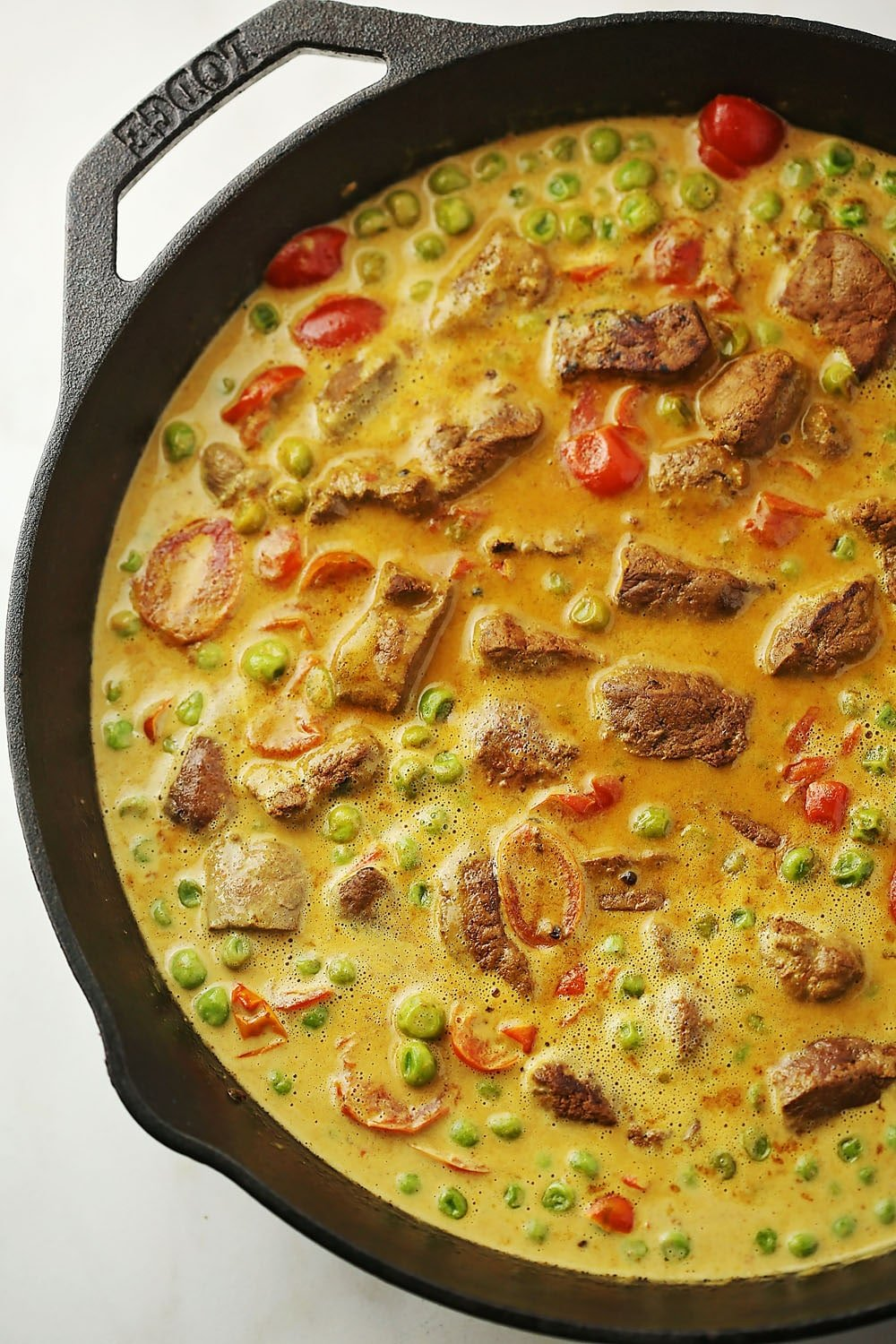skillet with liver, peas, and tomatoes in sauce