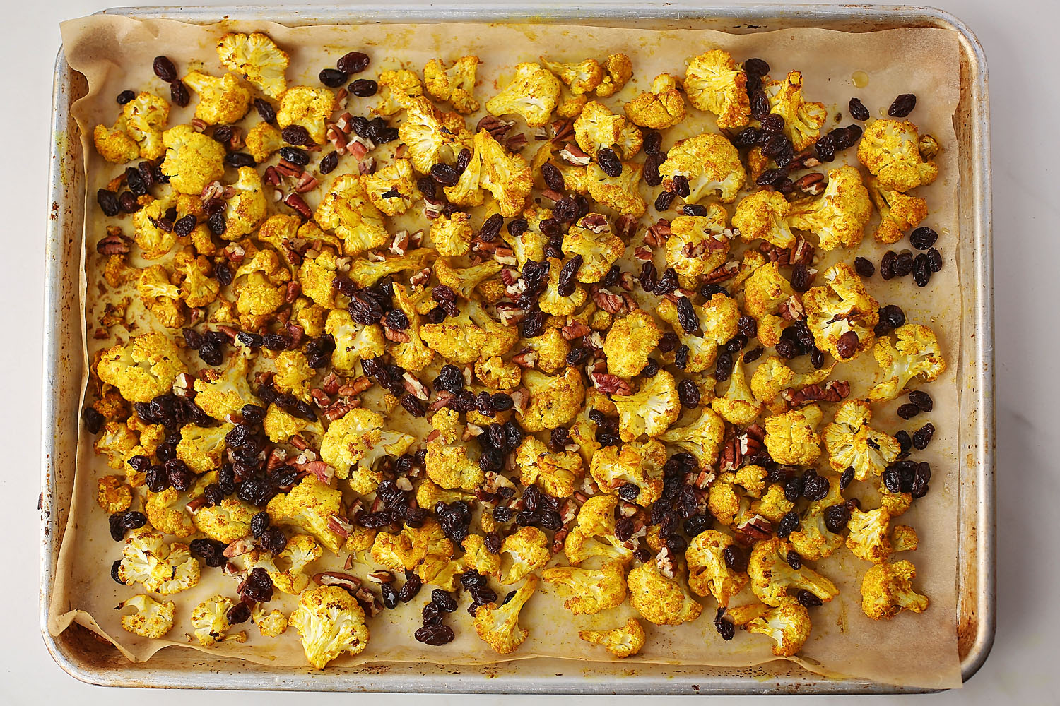 sheet pan with curry roasted cauliflower with raisins and pecans