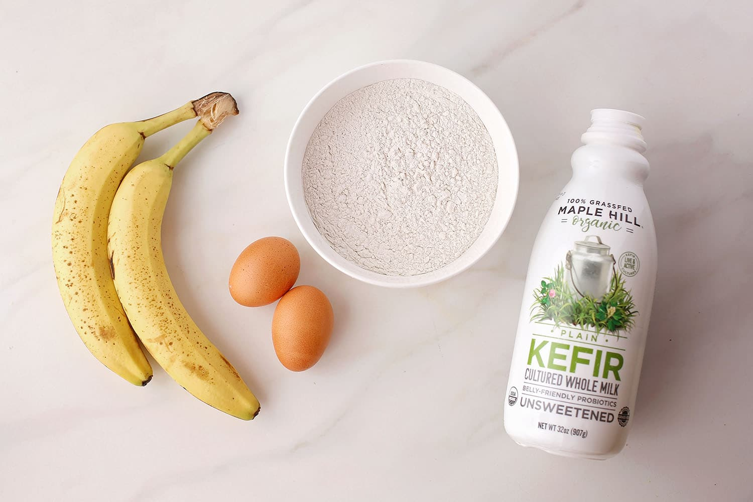 two bananas, bottle of kefir, bowl with flour, two eggs
