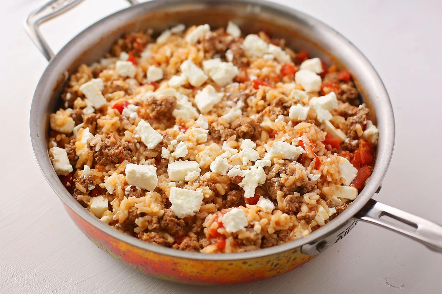 skillet with rice topped with crumbled feta