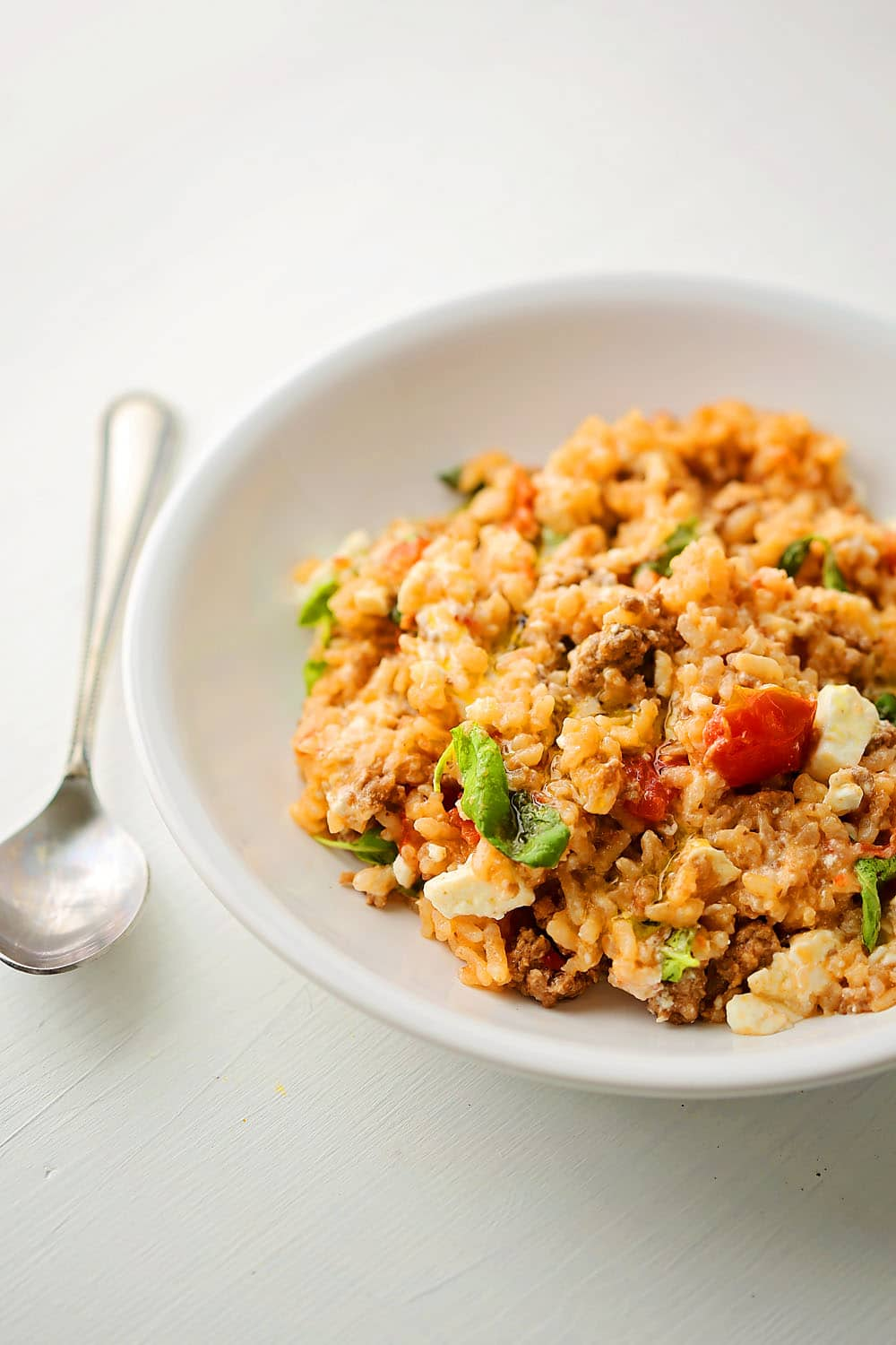 a white plate with rice and tomatoes