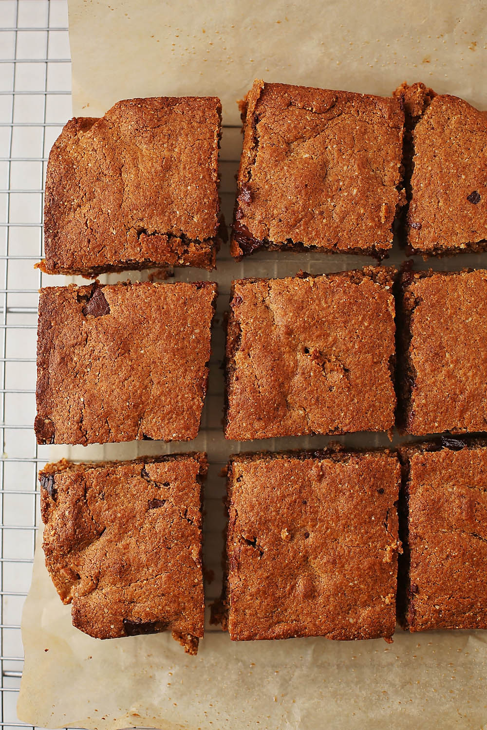 parchment paper with sliced almond butter blondies