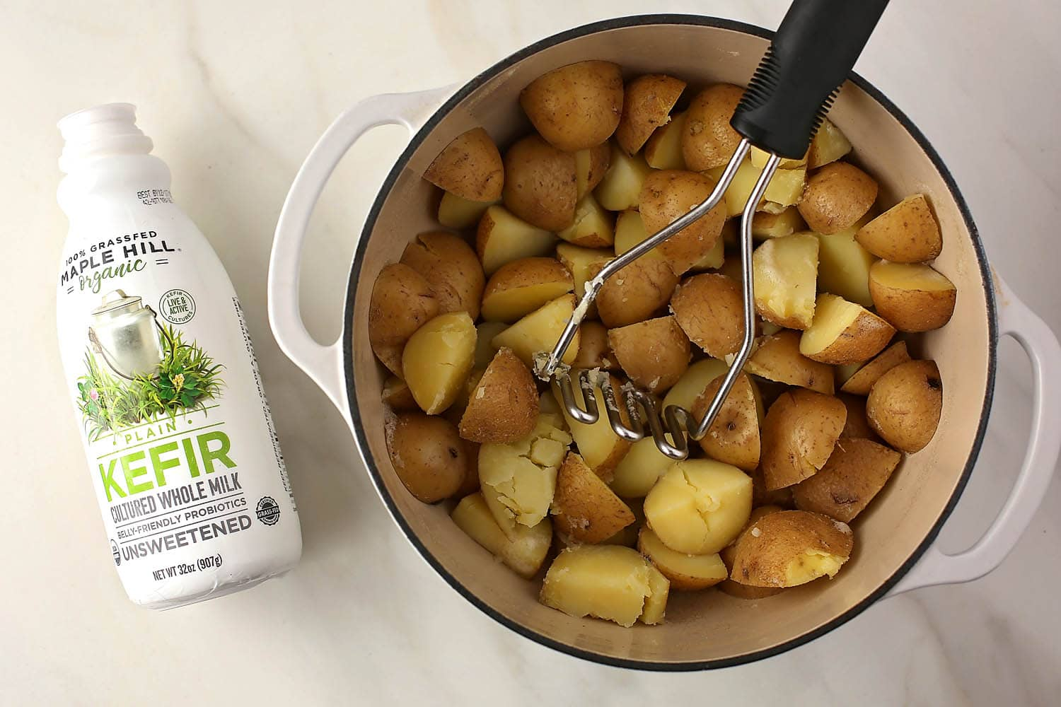 pot with boiled potatoes and kefir bottle next to it