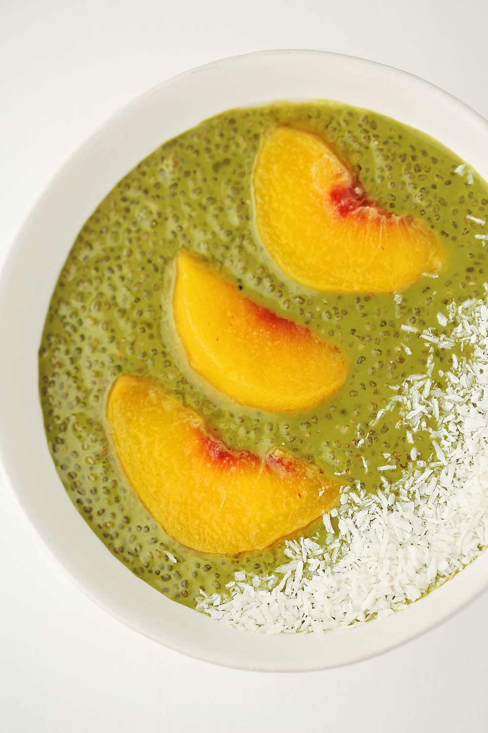 white bowl with matcha chia pudding and peaches