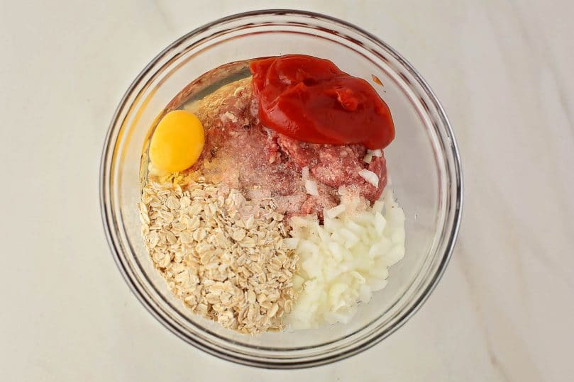 mixing bowl with ground beef, onions, oats and egg