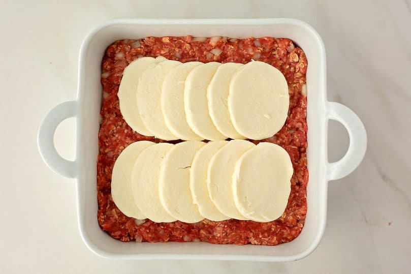 baking dish with ground beef layer and mozzarella cheese