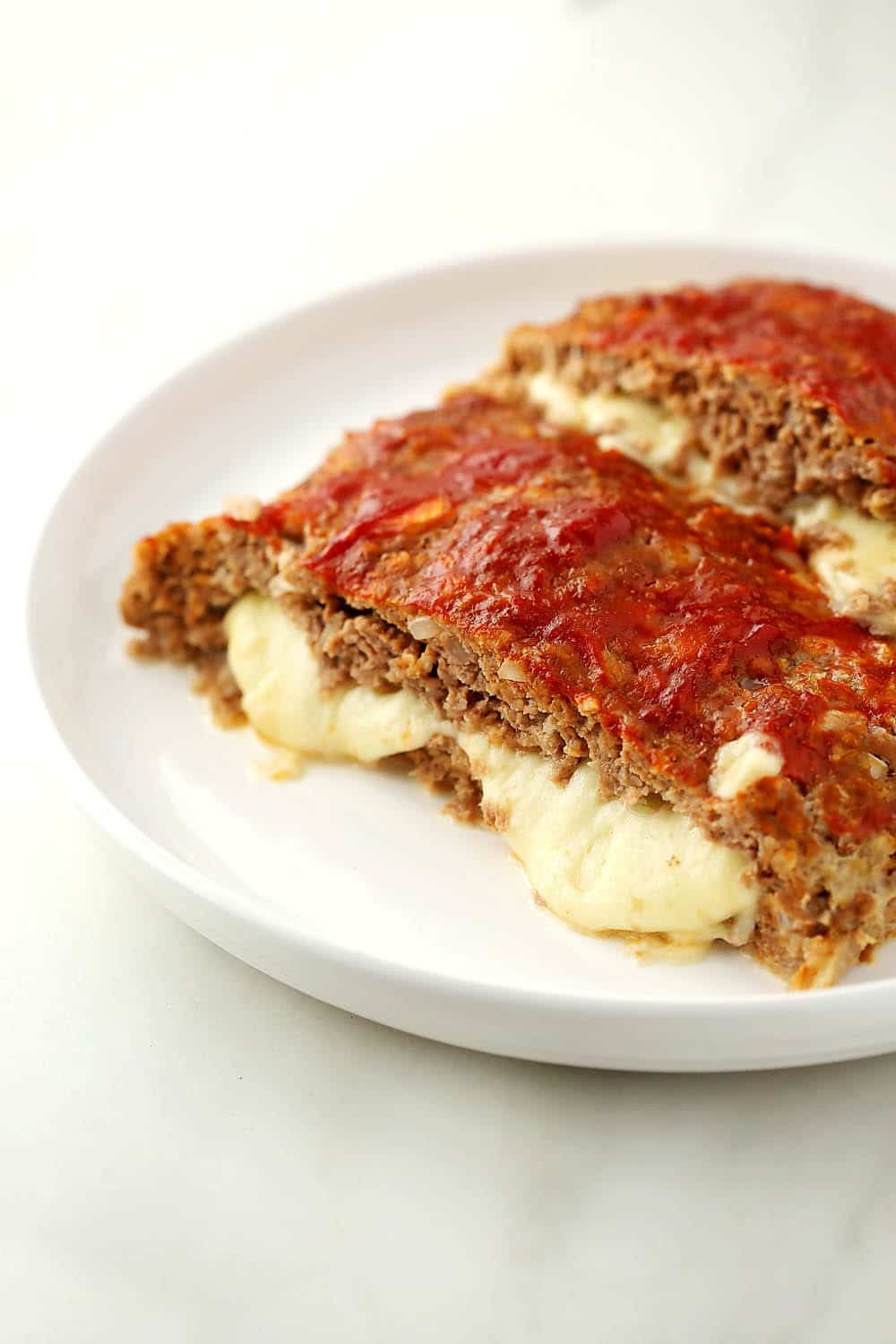 plate with meatloaf stuffed with melting cheese