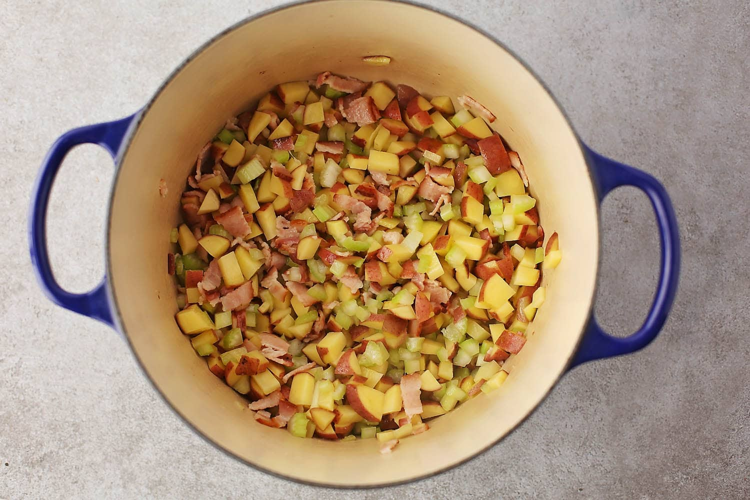 deep pot with fried bacon and vegetables
