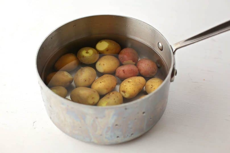 small saucepan with potatoes and water inside