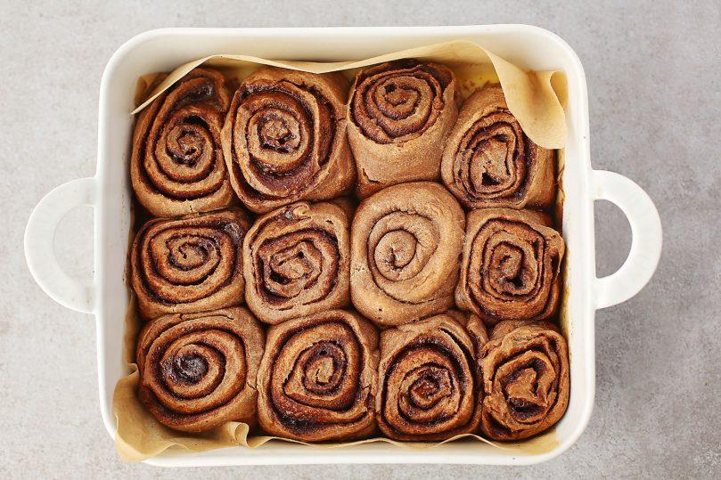 cinnamon rolls inside the white baking dish