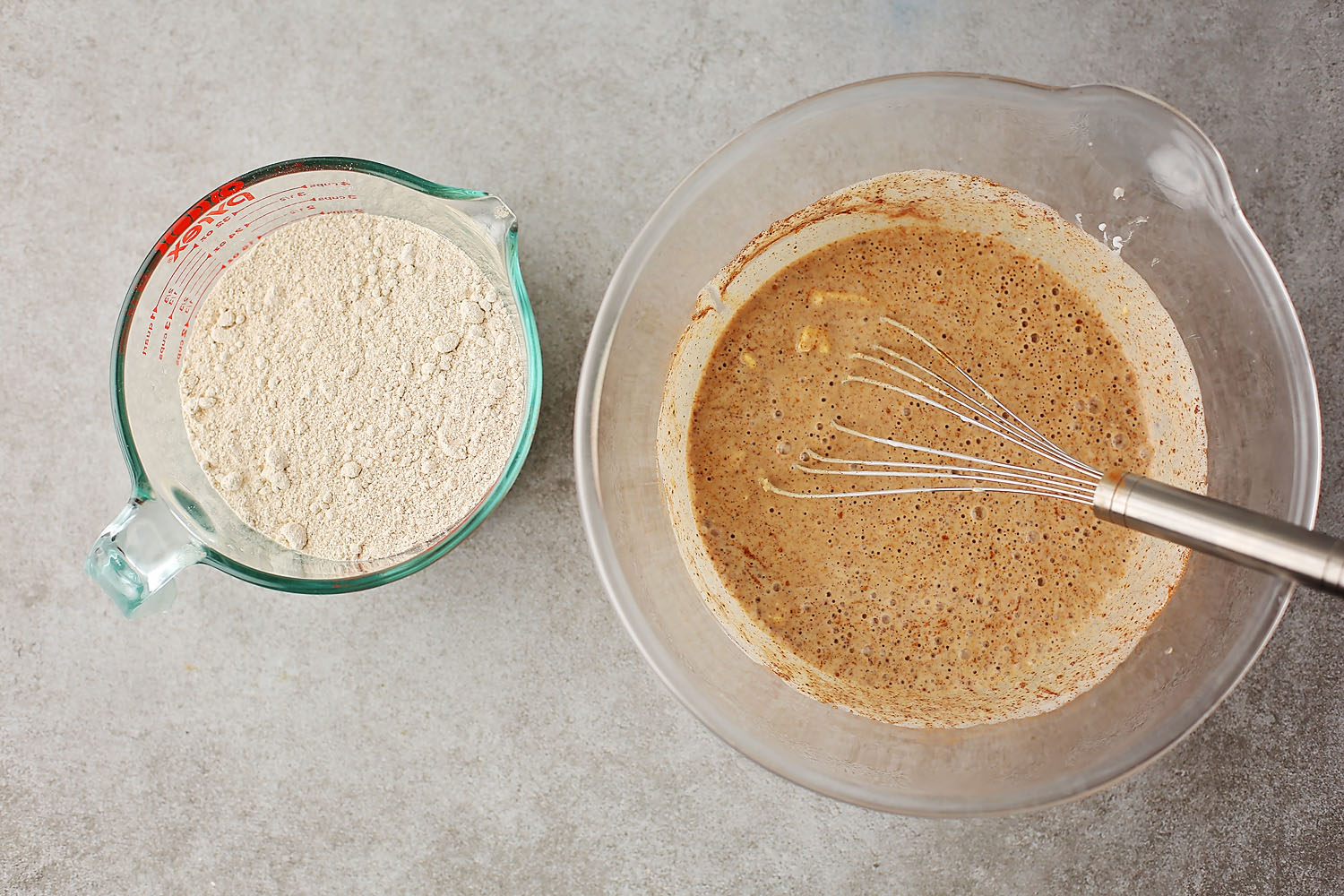 mixing bowl with egg, butter, cinnamon mixture and measuring cup with flour
