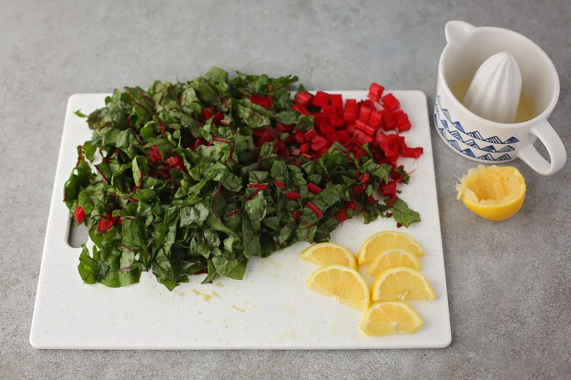 cutting board with diced chard and lemon slices